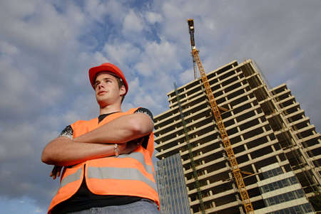 coordinating: Construction supervisor in safety helmet and reflex vest in front of construction site. Stock Photo