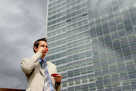 countenance: Young businessman having a break and drinking cup of coffee in front of business building.
