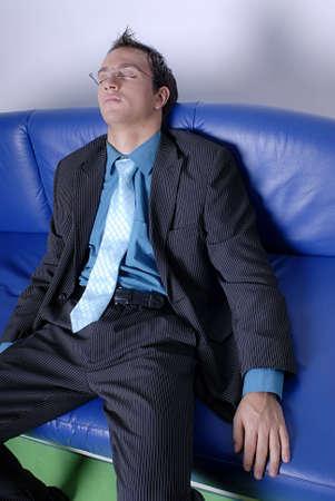 blue leather sofa: Un uomo d'affari vestito in completo sentivo addormentato sul divano in pelle blu.