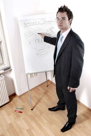 Handsome young businessman giving presentation at flipchart in office. photo