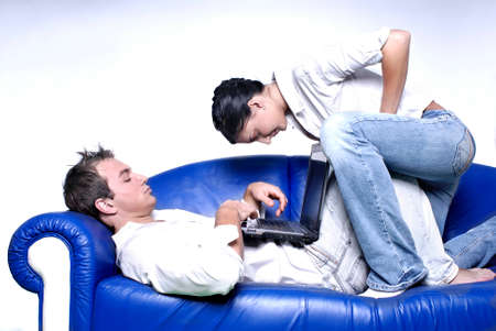 Young couple sitting in a sofa using a laptop Stock Photo - 2750678