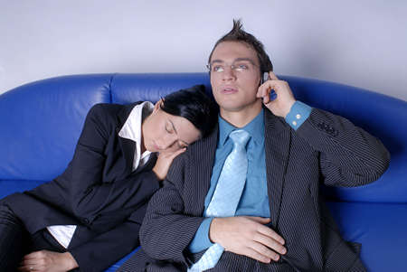 Young couple - business team woman laying on mans shoulder while he speak on phone photo