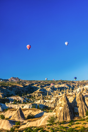 make known: Hot air balloons soaring over fairy chimneys. Cappadocia is known as one of the best places to fly with air balloons. Curvy conical shapes of the rocks in valley make feel fantastic. Anatolia, Turkey. Stock Photo