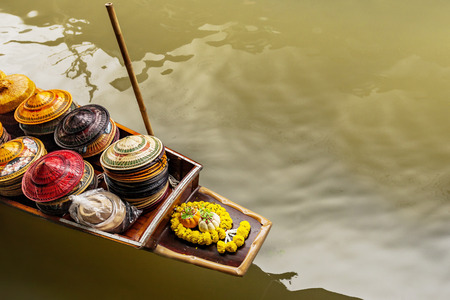 carrying the cross: A small raft carrying foods. Colors of raft, reflections of lights on the sea seem very beautiful. A cross decorated as flowers is on brown raft. Photo has taken at sunlight in summertime in Bangkok. Stock Photo