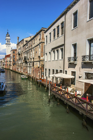 coffee houses: Venice canals and buildings with Venetian Gothic style. Sandals on green water. One of the coffee houses inside one of the buildings has table and chairs. Venice, Italy. Stock Photo