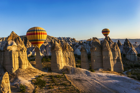 surreal landscape: Hotir balloons are landing among fairy chimneys, Cappadocia. Volcanic disasters created surreal landscape: wind and rain sculpted into sinuous valleys. Valley is natural place with unique topography. Stock Photo