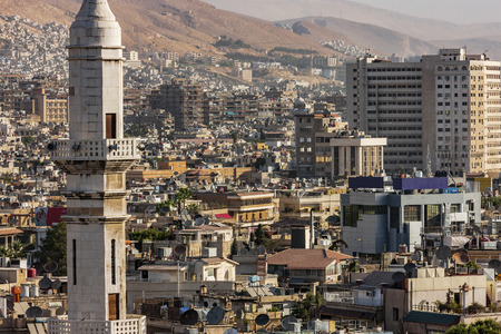 middle east war: A view of Damascus before the civil war. Many buildings were destroyed because of the bombs and clashes in the war in Syria. Houses are yellow and warm. Photo was taken at sunlight in a summertime. Stock Photo