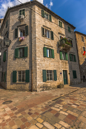 former yugoslavia: A building in historical city. Shutters of several buildings in the city of wood and green. The town square of the town built by old stones. The sun towards evening makes colors warm in Montenegro. Stock Photo