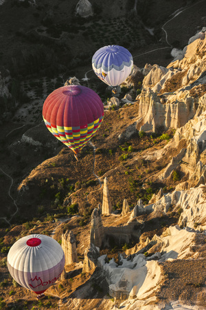 topography: Aerial view of hot air balloons over hoodoos. They had been formed by natural resources, like wind and rain in Cappadocia. Sunset shading on the valley. It is natural place with unique topography.