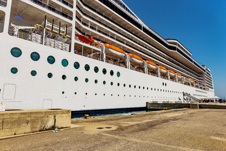 go inside: Side of the huge transatlantic. The magnificent ship carries thousands of people inside. Tourists who go down from the ship at anchor are hanging around the town in Venice, Italy.