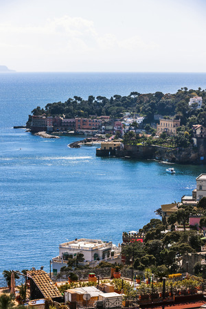 contributing: The shining sea in the Gulf of Naples. The colorful houses around the gulf liven up the photo. A boat is sailing, terraced roofs and flower pots on balconies are contributing the photo an exotic view.