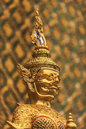 spiritual journey: Shining golden statue of the holy man. It has bright, warm tones. A traditional crown on its head. Decorations, patterns seem very beautiful. Geometrical shapes on the decorations of buddhist statues.
