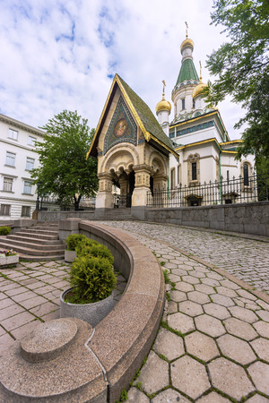 caving: Exterior view of Temple Sveti Nikolay with garden, Sofia, Bulgaria.Domes are coated with gold. It is Russian Revival Style church.Rising through the sky.The garden is floored with caving stones.