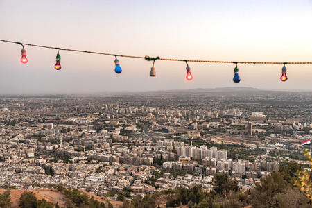 damascus: View of Damascus from the sky as one of oldest cities in Middle East region. Colorful lamps on the high hill which has a wedding ceremony. Cityscape can seen behind the lamps. Damascus, Syria. Stock Photo