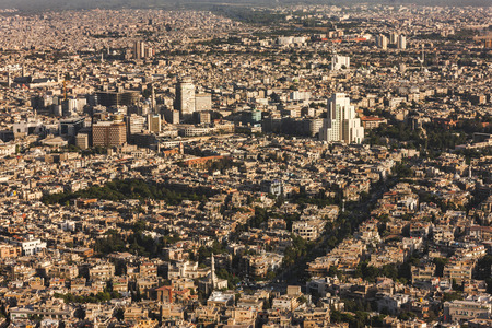 damascus: A view of Damascus before the civil war. Many buildings were destroyed because of the bombs and clashes in the war in Syria. Houses are yellow and warm. Photo was taken at sunlight in a summertime. Stock Photo