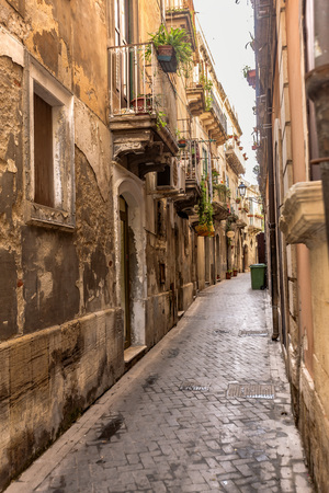 contributes: A narrow street was constructed by old stones at amazing sunlight. Stones on historical street are yellow, brown. Reflections, balconies, flowers contributes beauty to the landscape. Syracuse, Sicily. Stock Photo