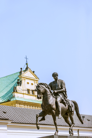 triangle shaped: A statue of soldier sitting on his horse and pointing forward at the centre of Warsaw. A yellow building with green roof behind the statue. There is a cross on the triangle shaped roof of building.