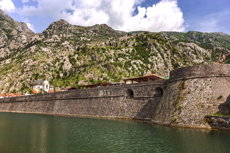former yugoslavia: Large and high walls that separated the lake dam and the town. Forest and mountains behind the old town. Clouds, water and colors looks very nice in a sunny day in Montenegro.