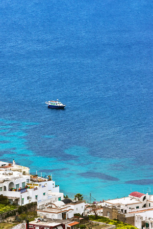 forefront: Boat on the sea at Capri Island coast, Italy. High angle shot. Buildings are at the forefront. The impressive sea is blue. A boat is on the sea.