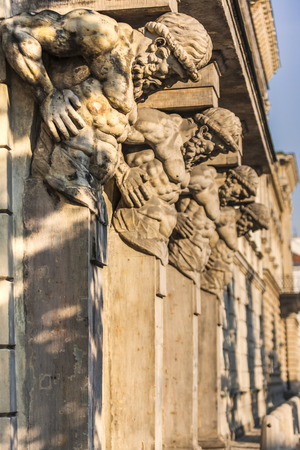 exaggerated: Historical and sacred sculptures. Muscles on human statues are exaggerated. Hands of the statues are on their waists and hold the stones by their backs. They seem very strong. Warsaw, Poland.