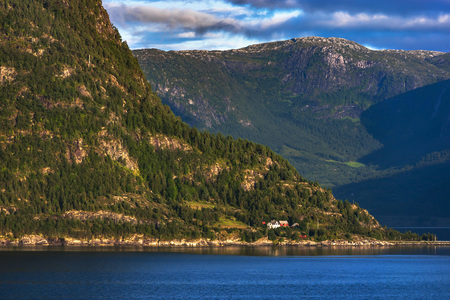 to seem: Amazing landscape of nature. Natural wonders, mountains, fjords and forests. Colors seem very beautiful. Dark blue color of sea and sunset lights can seen. Flam, Norway Stock Photo