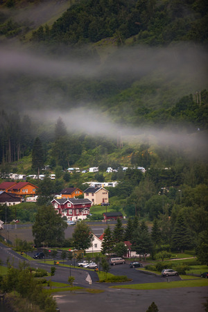 to seem: Amazing scenery of nature. Natural wonders, mountains, fjords and forests. Colors seem very beautiful.The town can seen behind foggy air. Flam, Norway Stock Photo