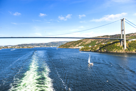 to seem: Scenery of a bridge, small sailboat and waves by cruise ship. A sunny day in summer time. Colors of sea and sky seem very beautiful. Bergen, Norway Stock Photo