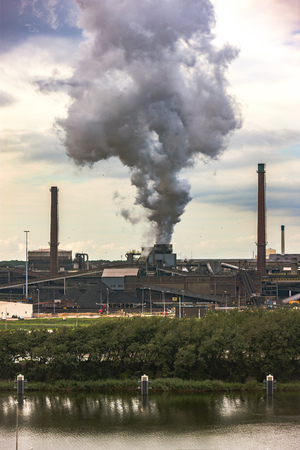 riverside trees: The dense smoke from the chimney of the factory was built far from the city. Smothers seem very big and gloomy. Green trees on the riverside. Factories have long chimneys in Amsterdam, Netherlands. Stock Photo