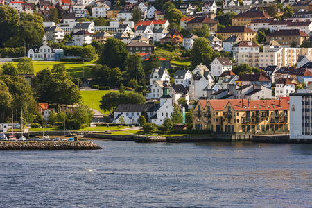 sea of houses: Spectacular view of the city from sea. Houses and green areas seem impressive. Seagulls flying over sea. Sunlight towards evening reflects from houses and creates a nice view. Bergen, Norway Stock Photo