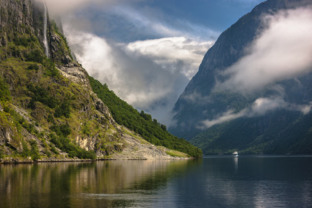 to seem: Amazing landscape of nature. Natural wonders, mountains, fjords and forests. Colors seem very beautiful. Sunlight reflect on mountains and clouds. Reflections and shades on sea. Flam, Norway