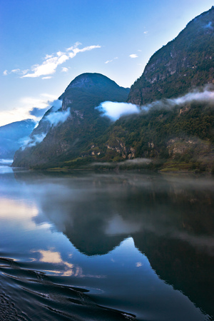to seem: Amazing landscape of nature. Natural wonders, mountains, fjords and forests. Colors seem very beautiful. Mountains and sea can seen between clouds and fogs. Flam, Norway Stock Photo