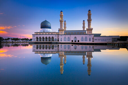Reflection of beautiful mosque at sunrise time in Malaysia photo