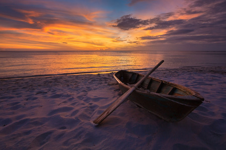 Wooden boat on the beach at sunset time photo