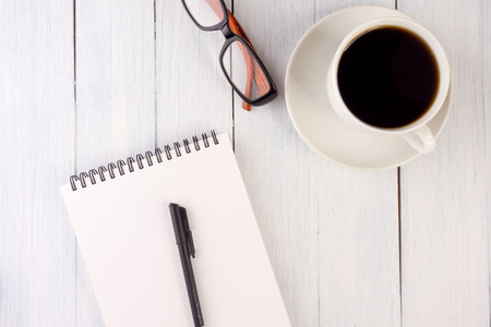 top view of coffee cup,glasses,note book,pen on the desk. Stock Photo