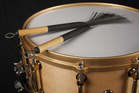 Brushes on a snare drum against a black background