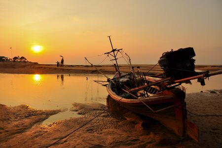 phangnga: The old fishing boat and sunset on the beach Phangnga Stock Photo
