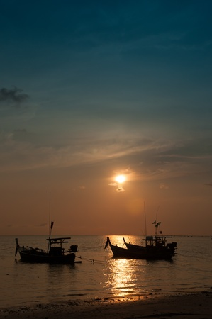 Fishing boats and the sea in the evening and sunset photo