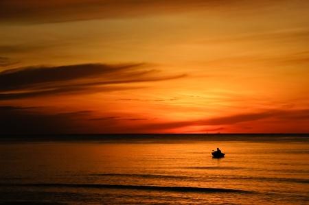 Boat at sunrise with fishing photo