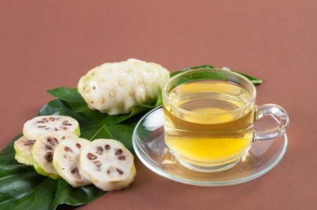 Noni juice fresh on brown background