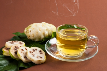 noni: Noni and Noni juice on brown background Stock Photo