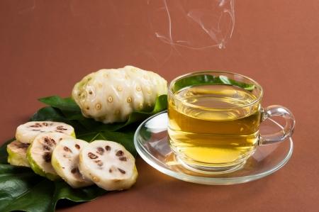 great morinda: Noni and Noni juice on brown background Stock Photo