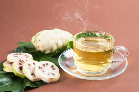 r sliced: Noni and Noni juice on brown background Stock Photo