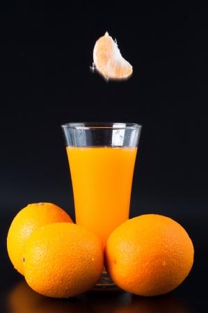 Fresh orange juice and oranges on a black background