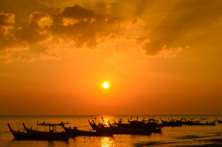 Silhouettes of fishing boats on the beach and sunset  Stock Photo