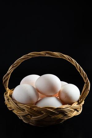 Fresh eggs in the basket on black background