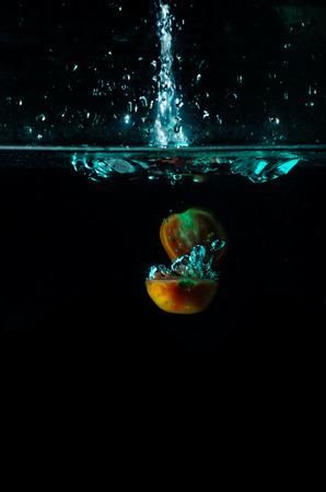Tomato water splash on black background photo
