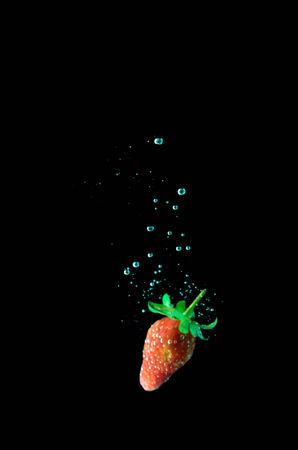 strawberry water splash on black background photo