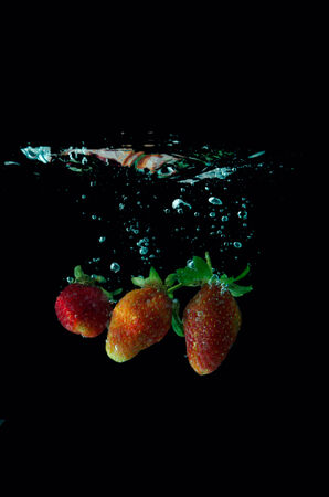 strawberry water splash on black background photo