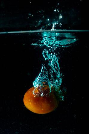 Tomato water splash on black background