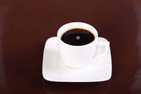 Coffee cup and saucer on black background